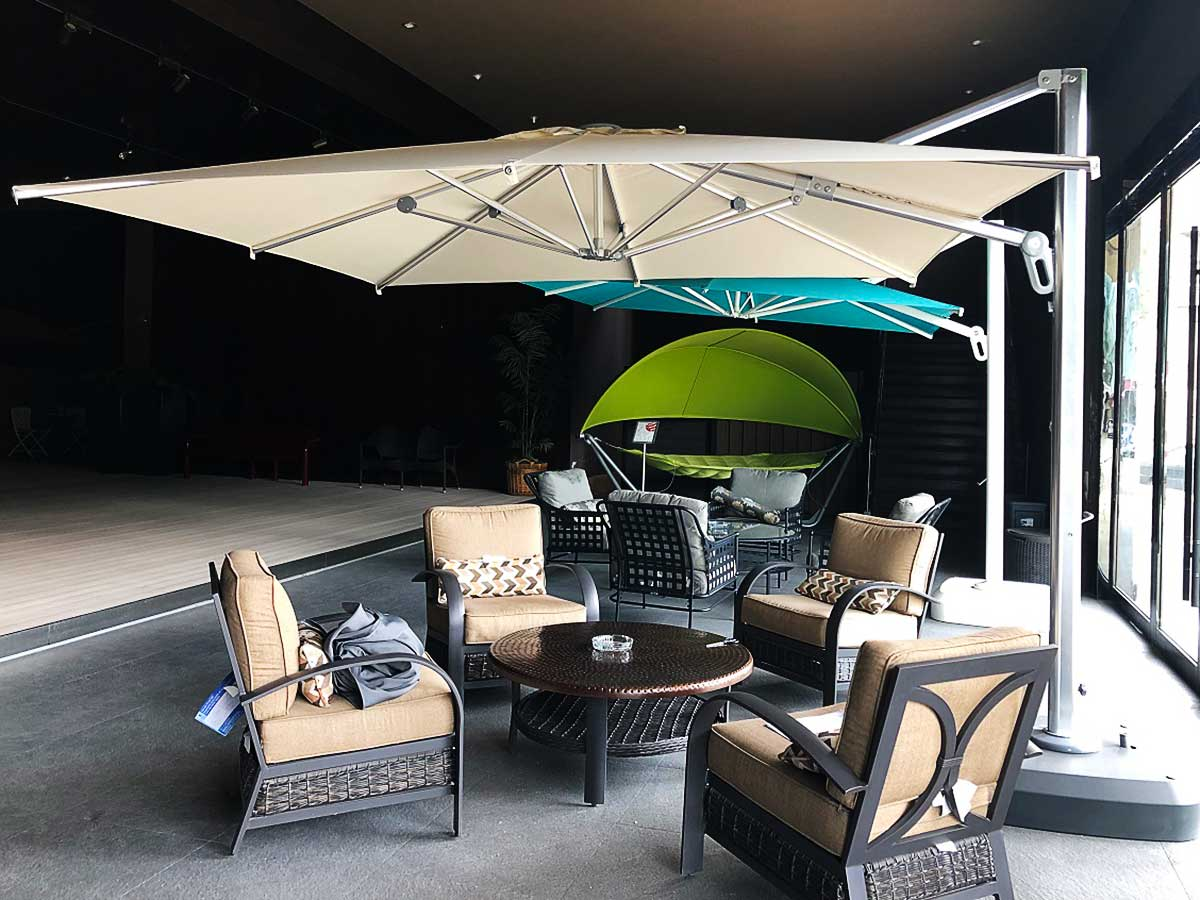 Cantilever style commercial umbrella positioned above patio furniture on display