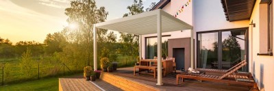 Louvered pergola on deck covering patio table